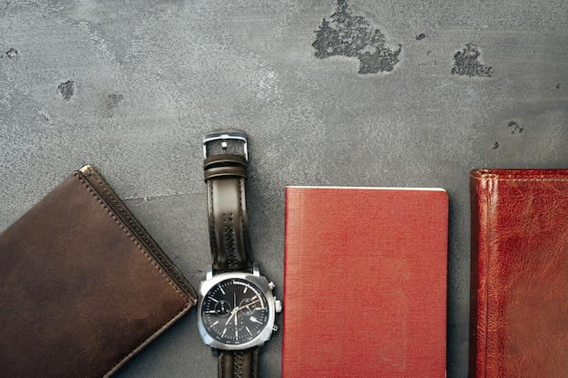 Acessórios do empresário, incluindo bloco de notas, relógio e bolsa em fundo cinza escuro.