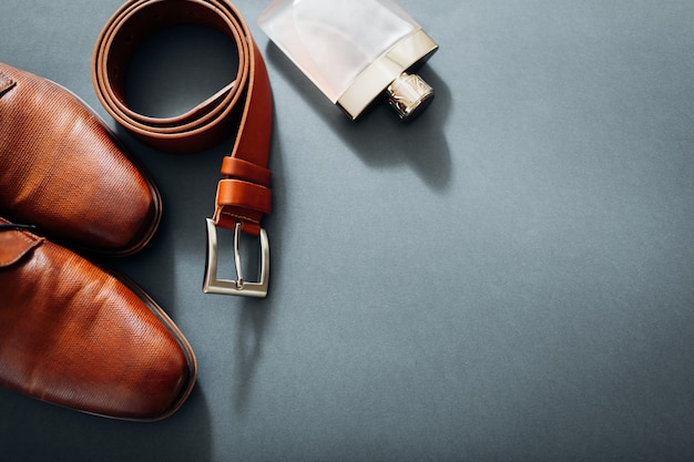 Acessórios do empresário. sapatos de couro marrom, cinto, perfume, anéis de ouro.