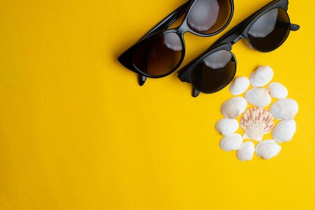 Acessórios do verão, shell e vidros de sol dos pares no fundo amarelo. férias de verão, lua de mel e conceito de mar.