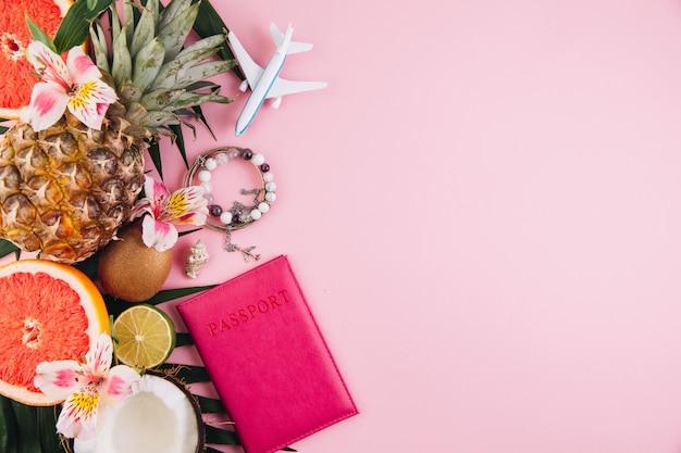 Acessórios do viajante e frutas tropicais no fundo cor-de-rosa na moda. cor brilhante de verão.