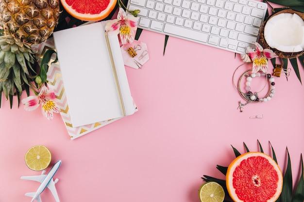 Acessórios do viajante e frutos tropicais na tabela cor-de-rosa do computador.