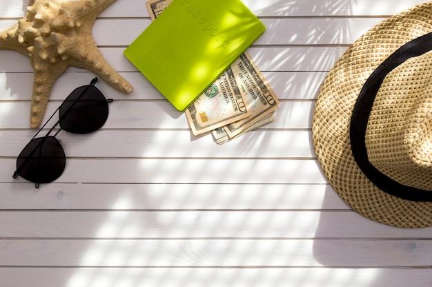 Acessórios do viajante - passaporte com dólares americanos do dinheiro do dinheiro, chapéu, sombra de ramos tropical da folha de palmeira.