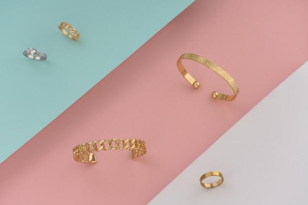 Acessórios dourados, pulseiras e anéis sobre fundo de papel em tons pastel