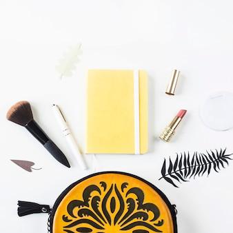 Acessórios e conteúdo de um saco feminino brilhante com ornamento laranja
