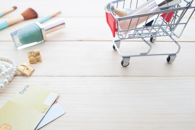 Acessórios e cosméticos da mulher no carrinho de compras com cartão de crédito na mesa de madeira,