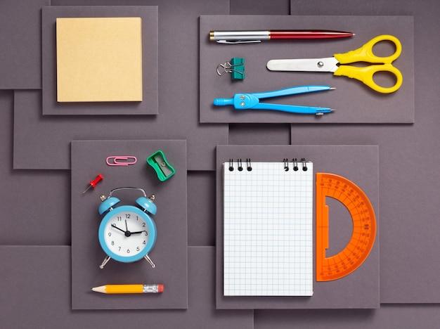 Acessórios e suprimentos escolares ou de escritório em uma textura de fundo de papel cinza