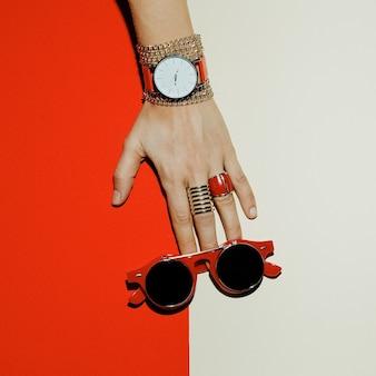 Acessórios elegantes. concentre-se no vermelho. relógios, óculos de sol, anéis.