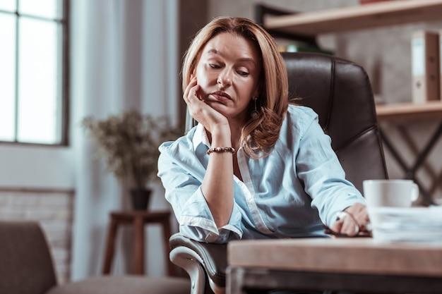 Acessórios elegantes. mulher madura com cabelos loiros e acessórios elegantes, sentindo-se triste e cansada