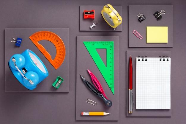 Acessórios escolares e material de escritório em fundo abstrato de papel cinza