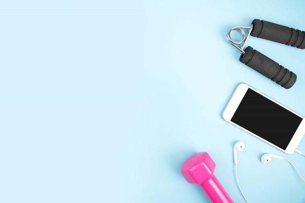 Acessórios esportivos com halteres, smartphones, fone de ouvido em um azul.