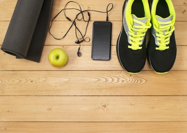 Acessórios esportivos para fitness no chão de madeira.