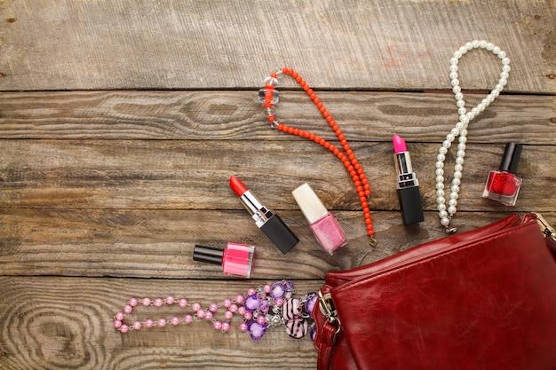 Acessórios femininos: bolsa de cosméticos, colar, unha polonês, batom.