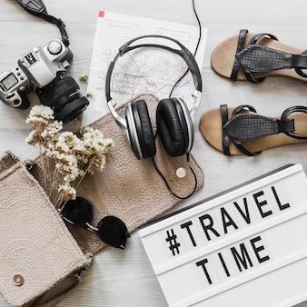 Acessórios femininos com texto de viagens e tempo na mesa de madeira