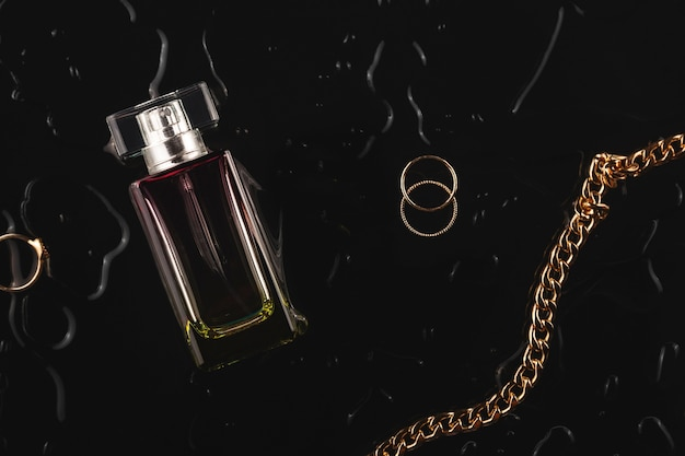 Acessórios femininos dourados e perfumes em um fundo preto entre gotas de água vista superior layout plano