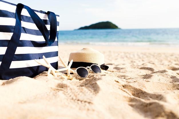 Acessórios femininos e bolsa na praia