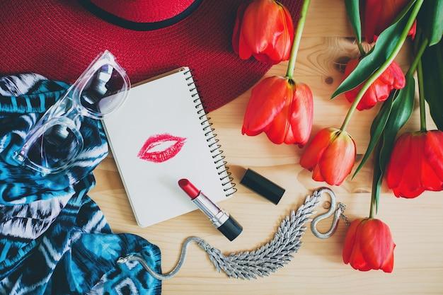 Acessórios femininos e tulipas vermelhas na mesa