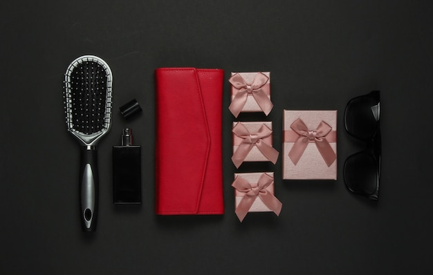 Acessórios femininos em um fundo preto. pente, óculos de sol, frasco de perfume, bolsa, caixa de presente. aniversário, dia das mães, natal. vista do topo