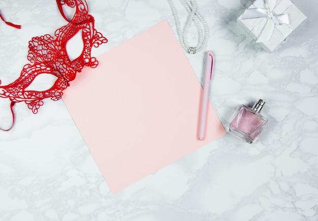 Acessórios femininos em uma mesa de mármore branca. uma folha de papel rosa, uma caneta rosa, um perfume, uma caixa de presente, pérolas, um copo de café e uma máscara vermelha em volta. layout para adicionar tags. vista superior, plana
