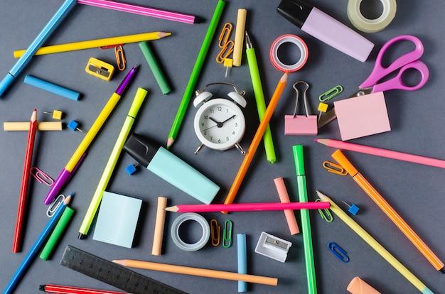 Acessórios infantis para estudo, criatividade e material de escritório em fundo escuro. volta ao conceito de escola