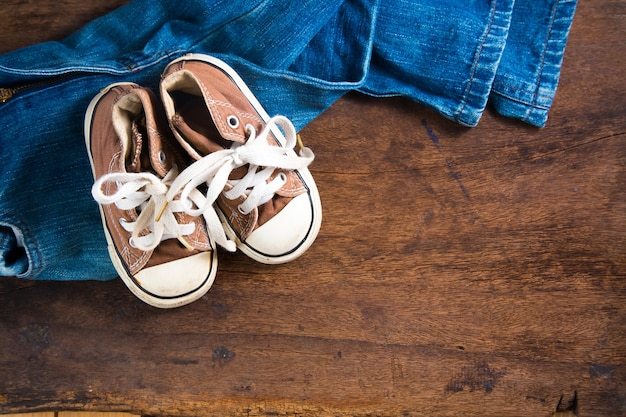 Acessórios, jeans e tênis em fundo de madeira
