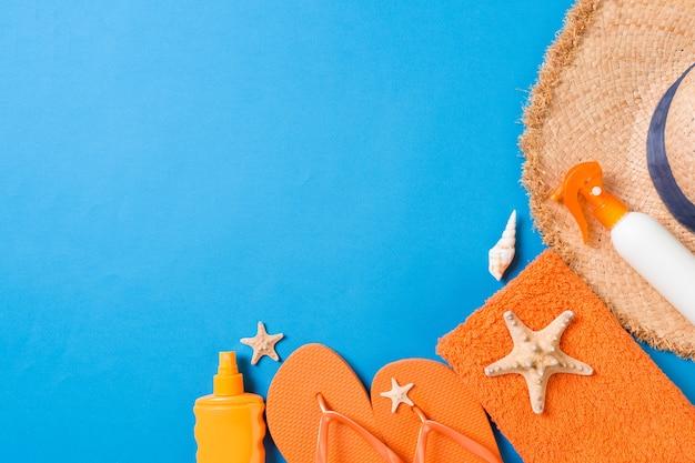 Acessórios lisos da praia do verão. creme de frasco de protetor solar, chapéu de palha, chinelos, toalha e conchas em fundo colorido. conceito de viagens de férias com espaço de cópia.