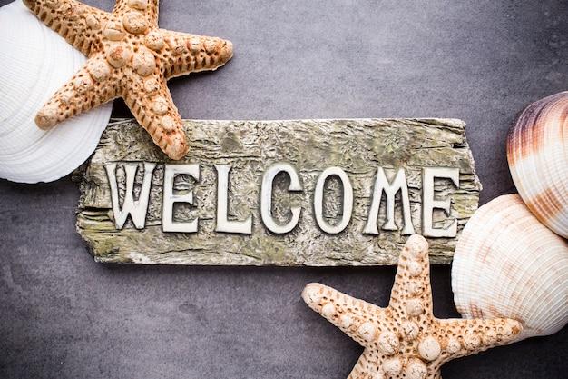 Acessórios marinhos de boas-vindas de inscrição, estrelas do mar, conchas.