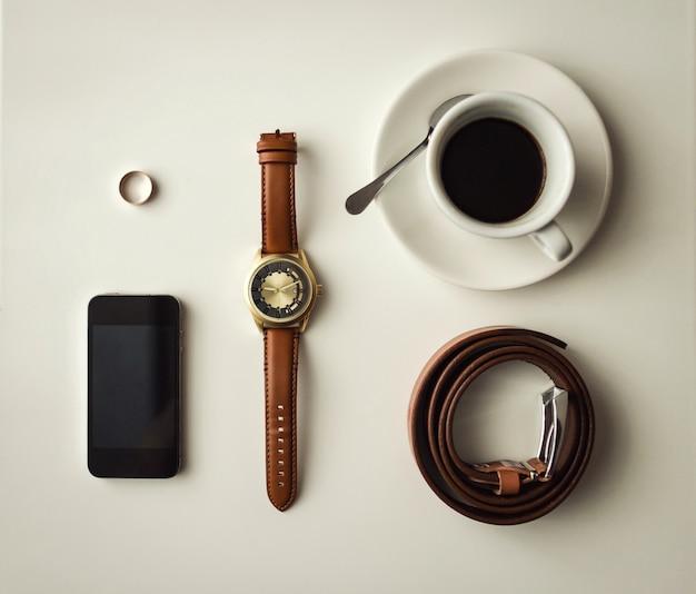 Acessórios masculinos, acessórios de homem de negócios, conjunto de coisas masculinas legais, acessórios de noivo, telefone, cinto, anel, relógios, uma xícara de café na mesa