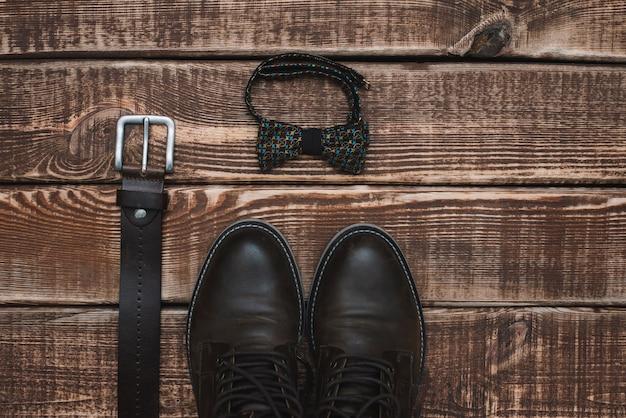 Acessórios masculinos cinto e gravata borboleta e sapatos de couro em uma mesa de madeira. postura plana.