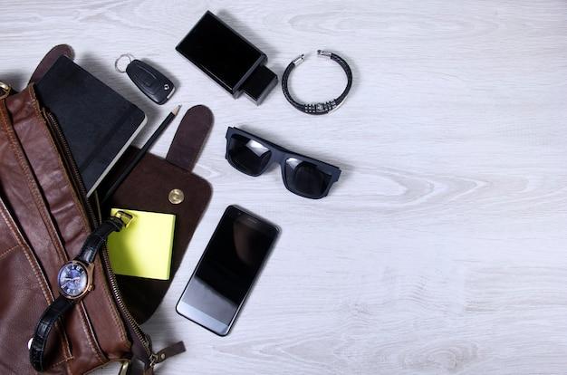 Acessórios masculinos com bolsas de couro marrom, cinto e óculos de sol na mesa de madeira sobre o fundo da parede