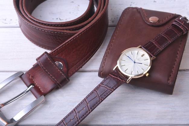 Acessórios masculinos com carteira de couro marrom, cinto e relógio.