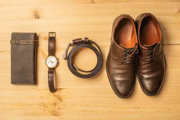 Acessórios masculinos com carteira de couro marrom, cinto, sapatos e relógio em superfície de madeira