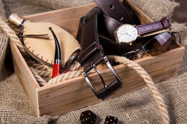 Acessórios masculinos com cinto de couro marrom, óculos escuros, relógio, cachimbo e frasco com perfume
