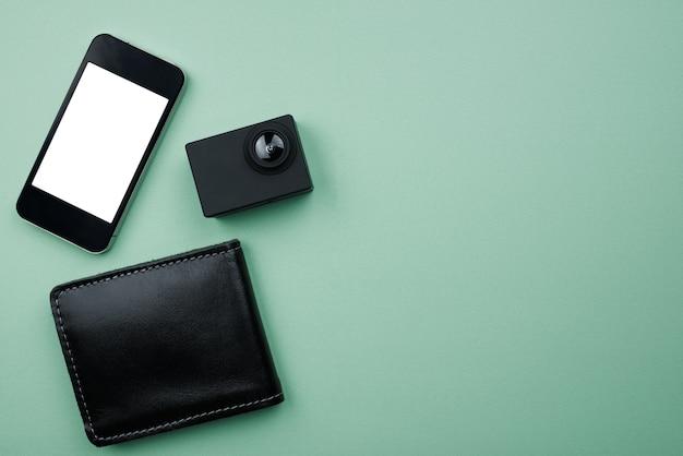 Acessórios masculinos de moda negra, relógio, celular, óculos de sol, carteira, fone de ouvido na mesa verde