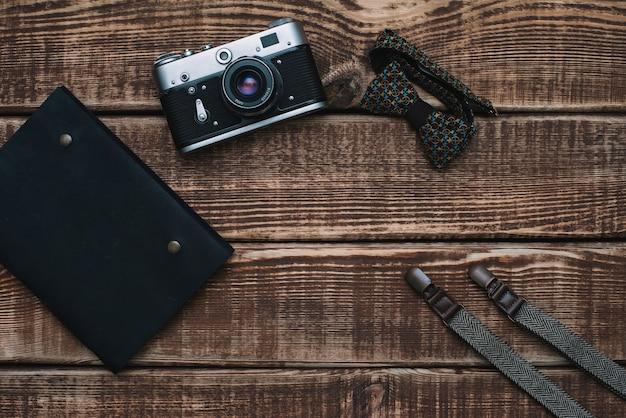 Acessórios masculinos gravata borboleta, carteira, câmera retro, suspensórios e bloco de notas e sapatos de couro em uma mesa de madeira. postura plana.
