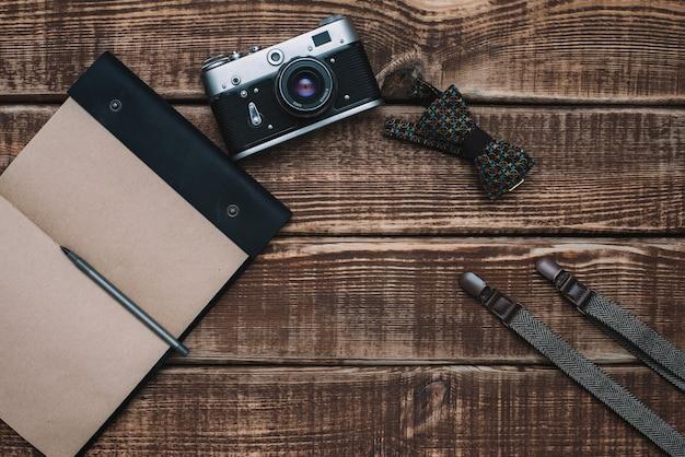 Acessórios masculinos gravata borboleta, carteira, câmera retro, suspensórios e bloco de notas em uma mesa de madeira. postura plana.