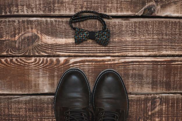 Acessórios masculinos gravata borboleta e sapatos de couro em uma mesa de madeira. postura plana.