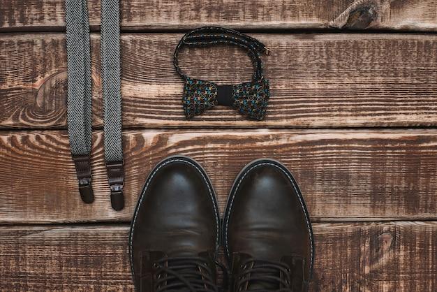 Acessórios masculinos suspensórios e gravata borboleta e sapatos de couro em uma mesa de madeira. postura plana.