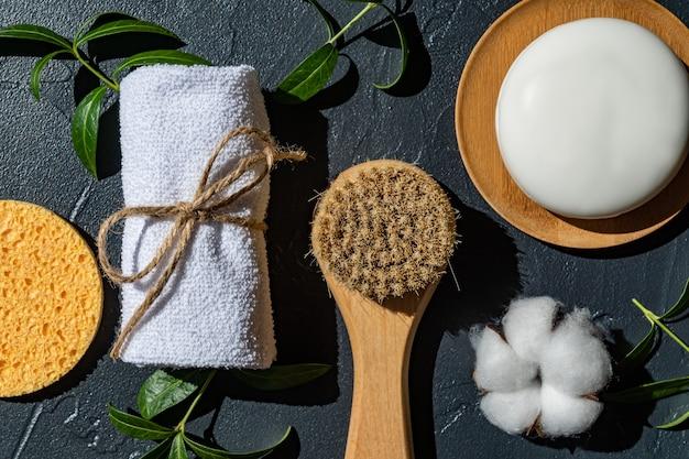 Acessórios naturais orgânicos do spa para tratamento facial e corporal com flor de algodão e folhas verdes sobre fundo preto. zero resíduos essenciais de banheiro, itens de plástico grátis.
