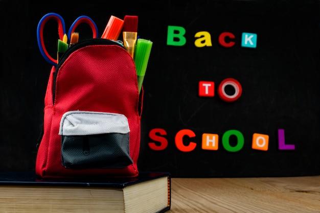 Acessórios no saco do estudante com a placa de giz preta. voltar ao texto da escola.