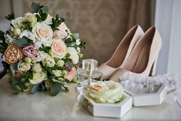 Acessórios nupciais como sapatos, bouquet, anel e perfume