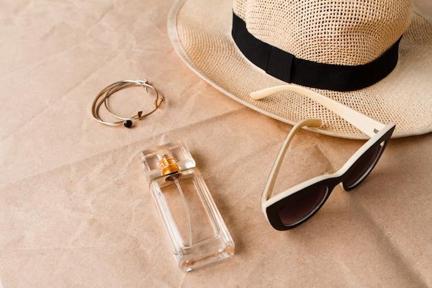 Acessórios óculos de sol perfume e chapéu sobre a superfície do artesanato