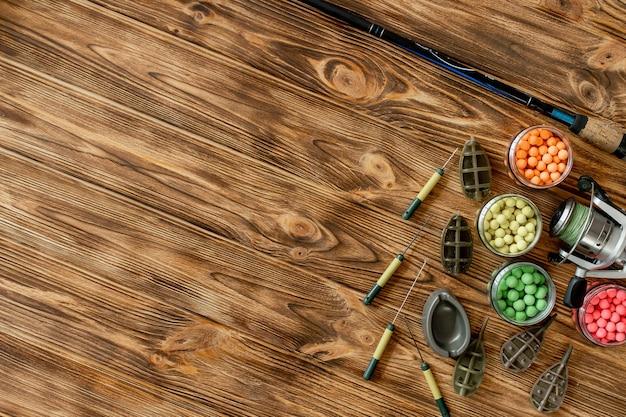 Acessórios para a pesca da carpa e iscas de pesca em pranchas de madeira copiam o espaço.