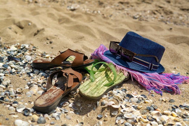 Acessórios para a praia, deitada na areia, chinelos masculinos e óculos de sol na areia da praia