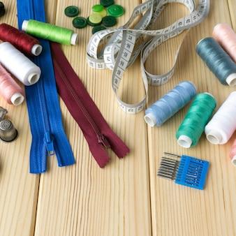 Acessórios para alfaiate. conjunto de material de costura na superfície de madeira.