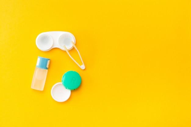 Acessórios para armazenamento de lentes: uma garrafa de líquido, recipiente aberto e pinças