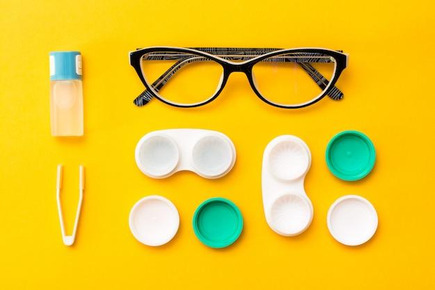 Acessórios para armazenamento de lentes: uma garrafa de líquido, recipientes abertos e pinças, óculos