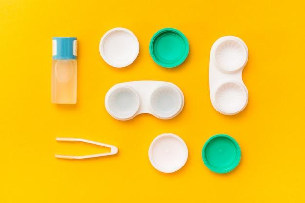 Acessórios para armazenamento de lentes: uma garrafa de líquido, recipientes abertos e pinças