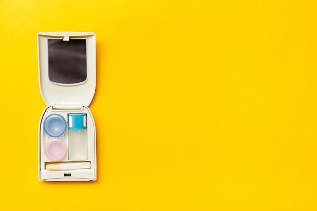 Acessórios para armazenamento de lentes: uma garrafa de líquido, um recipiente e uma pinça em um estojo
