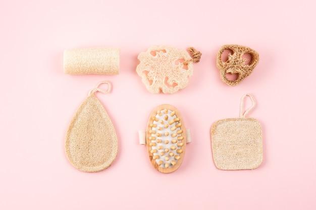 Acessórios para banheiro, esponja de bucha natural, escova de madeira no fundo rosa