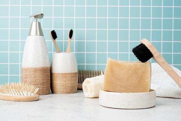 Acessórios para banho com escovas de bambu, sabonete artesanal, dispensador e escovas naturais na prateleira do banheiro, vista frontal